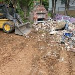 bobcat removes old building from private backyard