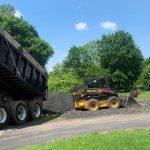 dump truck unloading gravel for bobcat